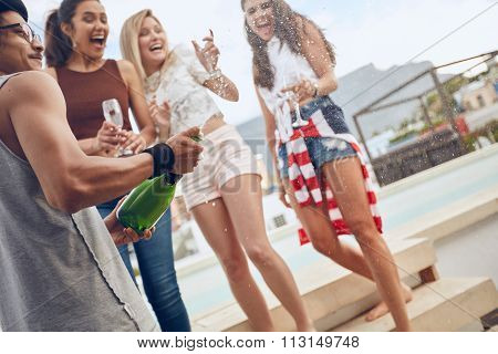 Man Opening A Bottle Of Champagne At Poolside Party