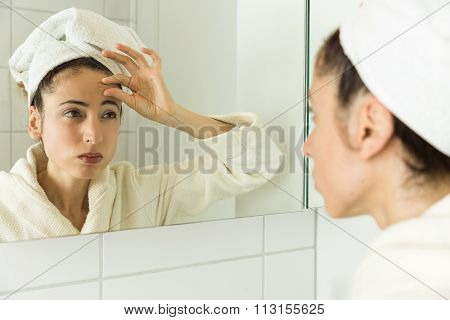 Woman Looking To Her Wrinkles In The Mirror