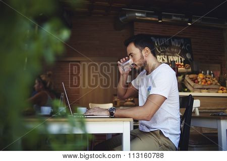 Young man entrepreneur drinking fresh water while working on laptop computer in comfortable cafe