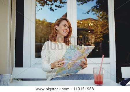 Happy Caucasian female searching on map the best route for visit city in her vacation time