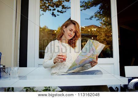 Attractive woman resting in sidewalk cafe and searching locations on city map during her vacations
