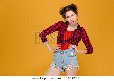 Thoughtful serious beautiful young woman in checkered shirt and jeans shorts standing with hands on waist over yellow background