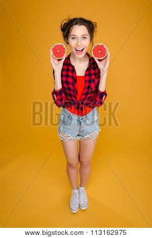 Full length of cheerful pretty young woman in checkered shirt and jeans shorts standing and holding two halves of grapefruit over yellow background