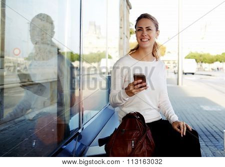 Cheerful female tourist using mobile phone for view map via network and continue her walk