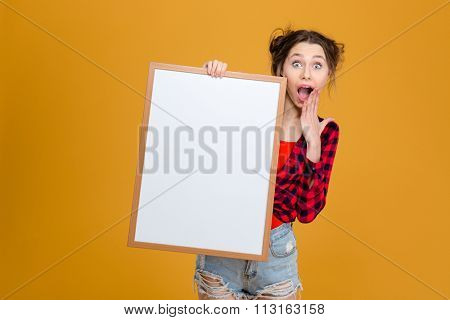 Amazed happy young woman in checkered shirt and jeans shorts holding blank board over yellow background