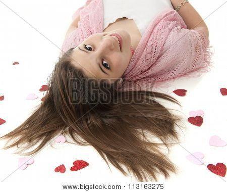 A beautiful teen girl on her back, looking up at the viewer.  Her head is surrounded by sparkly red and pink hearts.  On a white background.
