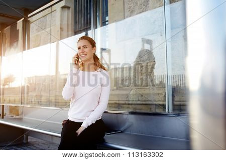 Gorgeous cheerful woman in good mood calling via cell telephone while sitting outdoors
