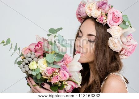 Attractive tender young woman in roses wreath holding and smelling beautiful bouquet of flowers over white background