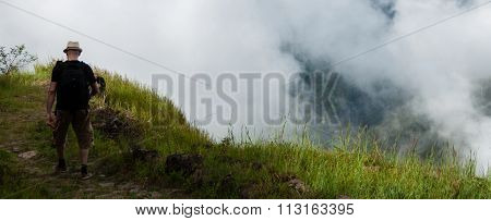 White man with black shirt and hat walking along a cliff above the clouds on mountain in cape verde