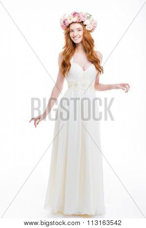 Full length of beautiful smiling young bride with long red hair in white dress and wreath of pink roses standing over white background