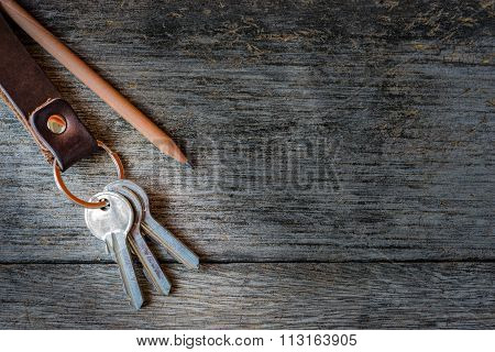 Key Chain And Pencil On Wooden Background.