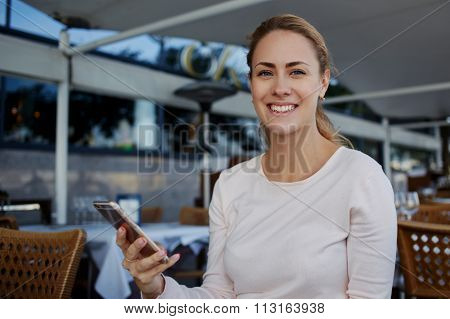 Charming young female with beautiful smile holding mobile phone while sitting in cozy restaurant