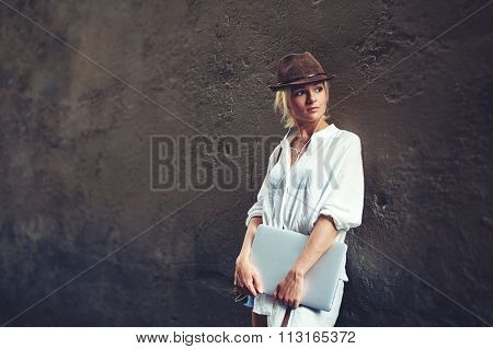 Hipster girl with net-book listening music in headphone