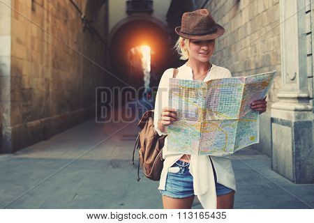 Happy female tourist searching road to hotel on atlas in a foreign city during vacation