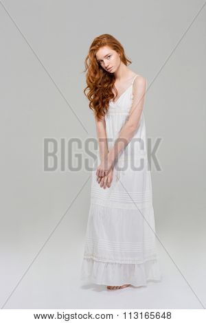 Full length portrait of a charming redhead woman in dress standing over gray background