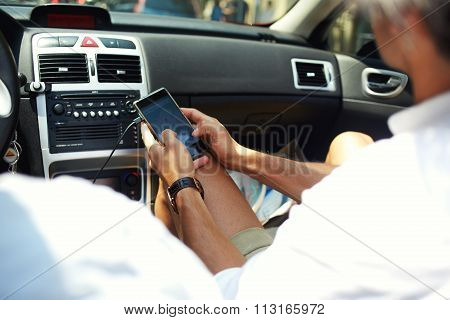 Cropped shot view of man checking location map on cell telephone while sitting near the driver