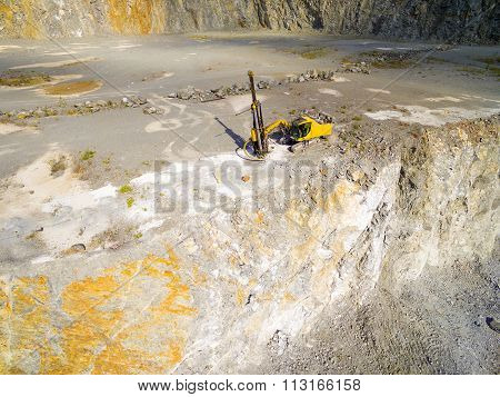 Aerial view of working drill in the opencast mine. Camera flight over industrial landscape. Use drones to inspect of mining area. Technology theme.