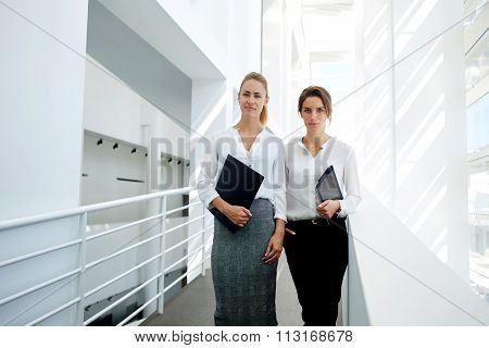 Woman lawyer with touch pad standing near her co-worker in office interior
