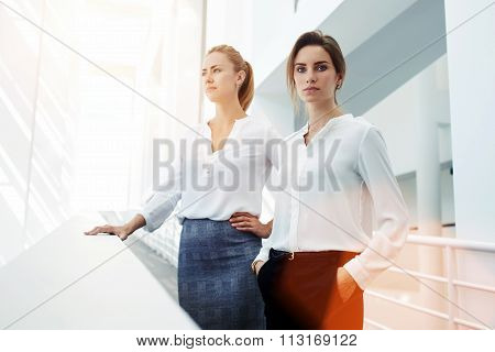 Successful women entrepreneurs with serious look posing while standing in modern office interior