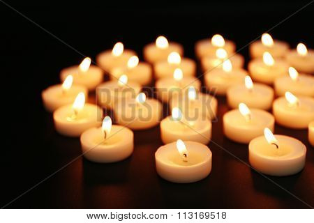 Alight candles in a row on black background