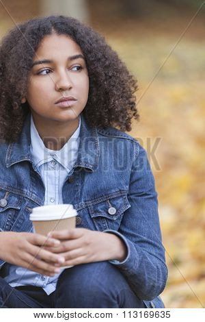Beautiful mixed race African American girl teenager female young woman drinking takeaway coffee outside sitting in a park in autumn or fall looking sad depressed or thoughtful