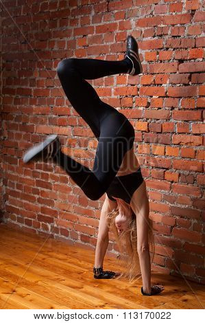 Fitness Model In Black Top And Leggings Performing Handstand