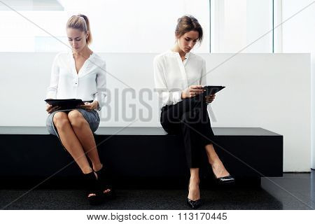 Female rivals preparing for interview with digital tablet and documents