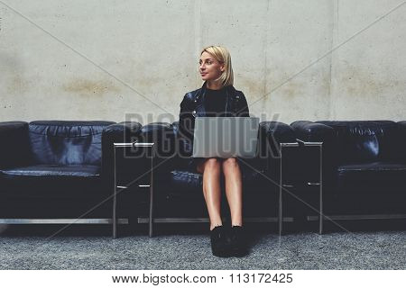 Female freelancer in good mood dreaming about something while holding on knees open net-book