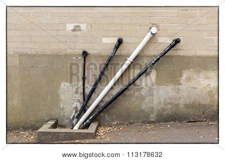 A Photo Of Black And White Angular Water Pipes On A Beige Brickwork Wall With A White Border