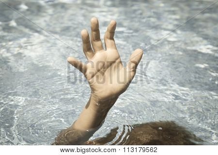 Sinking person calls for help. Hand out of the water.