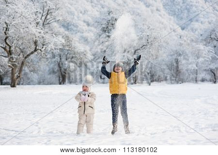 boy throws snow above the head being near the girl