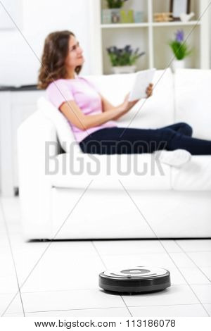 Cleaning concept - automatic robotic hoover clean the room while woman relaxing with tablet, close up