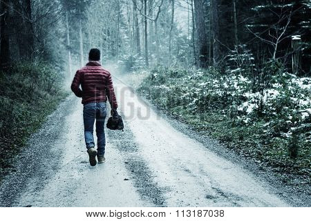 Single Man Walking Through A Forest Landscape In A Country Footpath