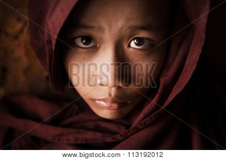 Close up face of  young novice monk covered with robe, low light with noise setting, Bagan, Myanmar.