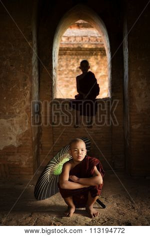 Portrait of young novice monks inside ancient Buddhist temple, Bagan, Myanmar.