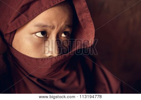 Portrait of young novice monk inside Buddhist temple, low light with noise setting, Bagan, Myanmar.