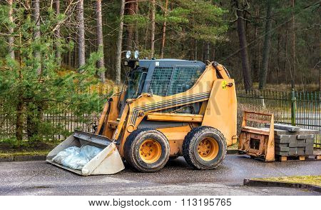 Bobcat or skid loader parked in forest