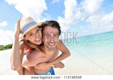 Man giving piggyback ride to girlfriend on Caribbean beach