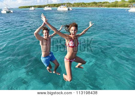 Cheerful couple jumping into water from boat