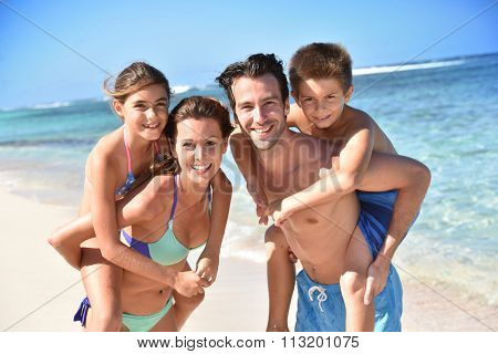 Portrait of cheerful family at the beach, piggyback ride