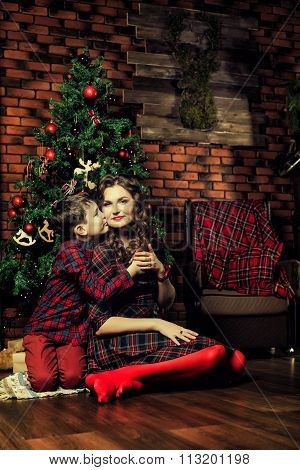 Family celebration of the New Year. The mother and son near a Christmas tree. Giving gifts. Holiday
