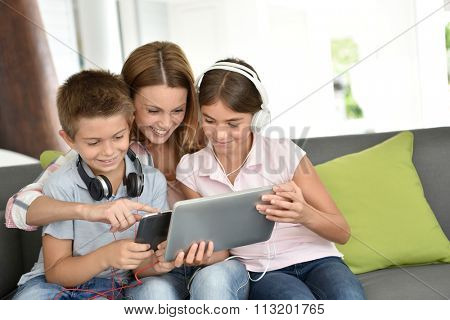 Mother with kids playing with digital tablet