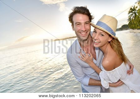 Romantic couple walking on the beach at sunset