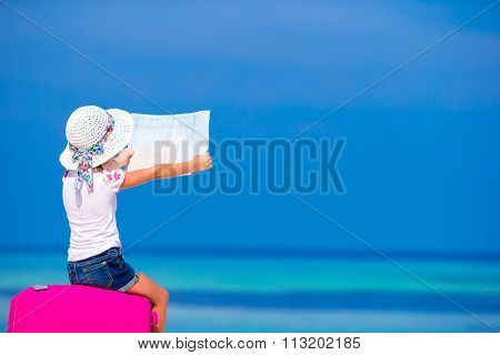 Little adorable girl with big luggage and mapduring beach vacation