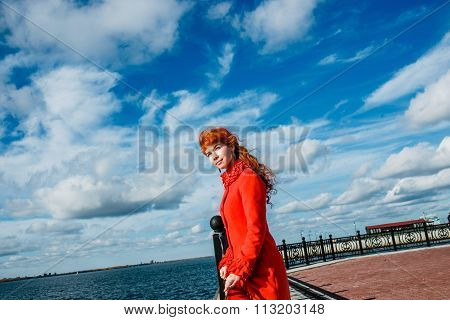 portrait of young redhead woman in red winter coat against the blue sky