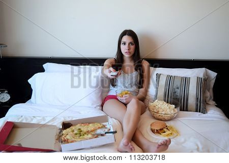 Young Woman Watching A Scary Movie On Tv In Bed