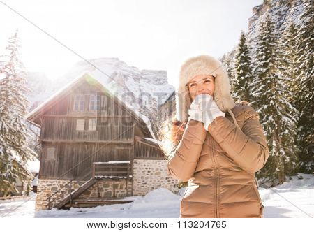Woman Warming Hands With Breath Near Cosy Mountain House