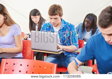 Student with laptop in class at school learning
