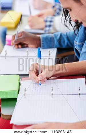 Students taking notes in class with their notebooks