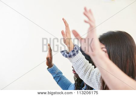 Students in class raise their hands in high school